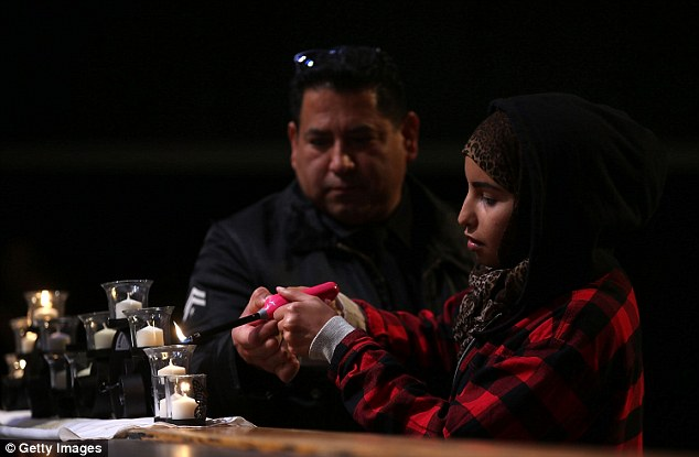 A Los Angeles police officer helps a mourner light a candle for the 14 people killed by Malik and Farook, during a United We Stand vigil at Granada Hills Charter High School on December 5