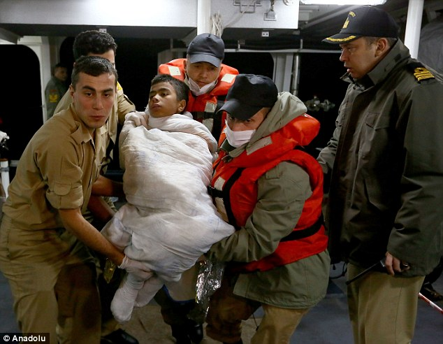 Rescue: A child is lifted to safety on board a Turkish Coast Guard ship. On the same night, 12 children drowned after the dinghy they were in capsized on its way to Greece