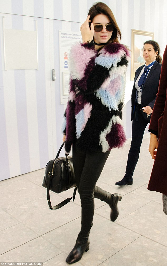 Travel in style: Making her way through Heathrow airport, the 20-year-old Victoria's Secret beauty cut a casually chic figure in a pair of skin tight leather jeans and multi-coloured fleece jacket