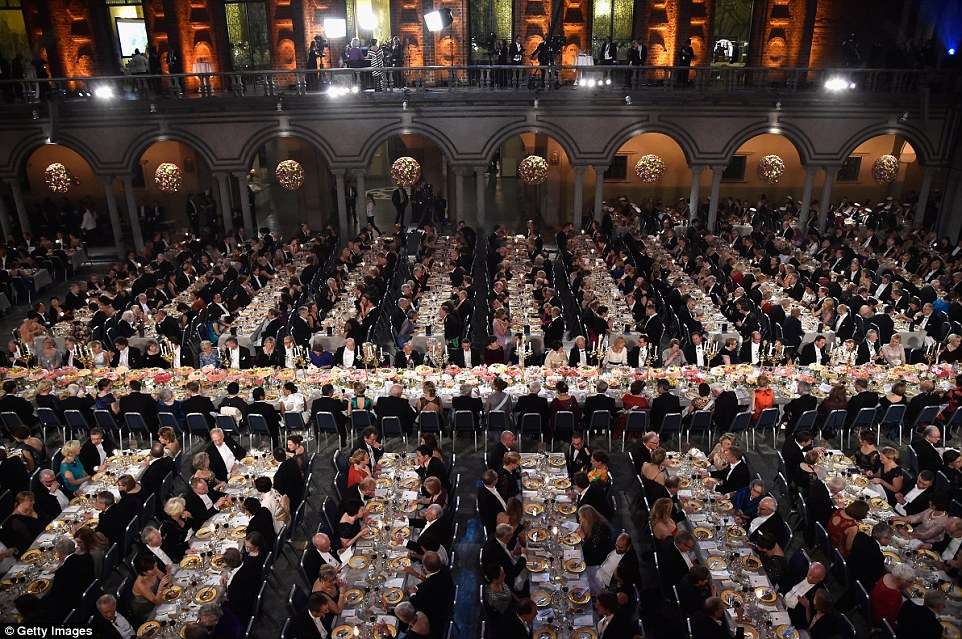 Guests dine on suitable opulent gold plates inside the packed city hall while dressed in their finery
