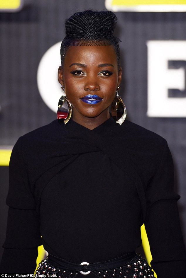 Edgy: Lupita set off her daring dress with a slick of metallic lipstick and giant gold earrings
