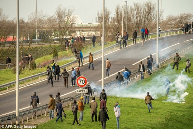 French police try to disperse migrants and refugees on one of the roads leading up to the Euro Tunnel in Calais