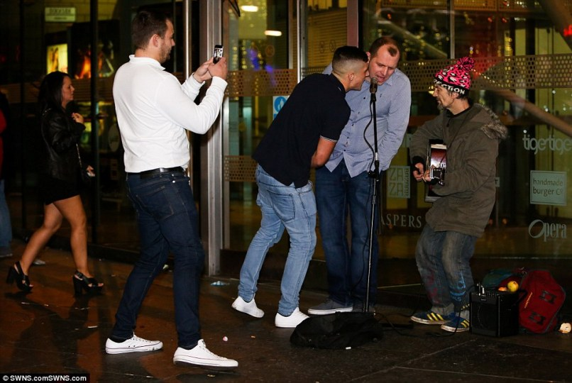 Singing to the tune: These part-goers sing some karaoke in the street outside the tiger tiger nightclub in Newcastle where a busker entertains the crowds on one of the busiest nights of the year