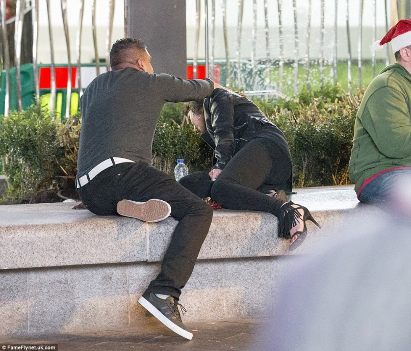 End of the night: A man holds a woman's hair back as she leans over a wall in central London following a night out