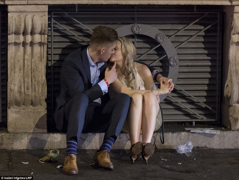 Smooch: A couple share a kiss as they sit on the curb on a street in central London as thousands of revellers hit the streets
