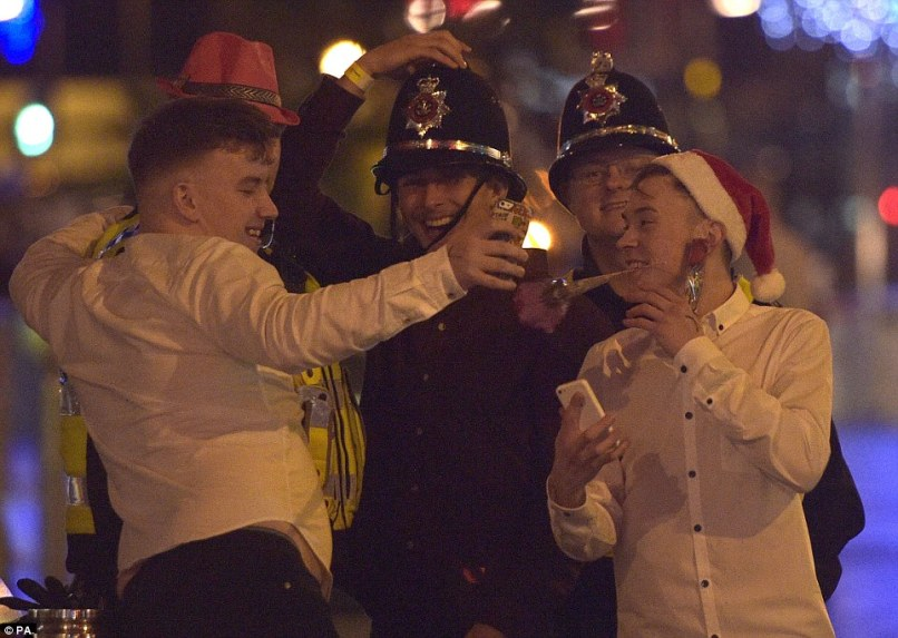 Say cheese: A group of men pose in police and Santa hats as they take a selfie with police officers on St Mary Street in Cardiff