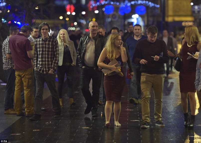 Busy: Streets were packed with revellers as people across the country celebrated the start of Christmas. In Cardiff a woman is pictured carrying her shoes in her hand as she walks along the wet floor