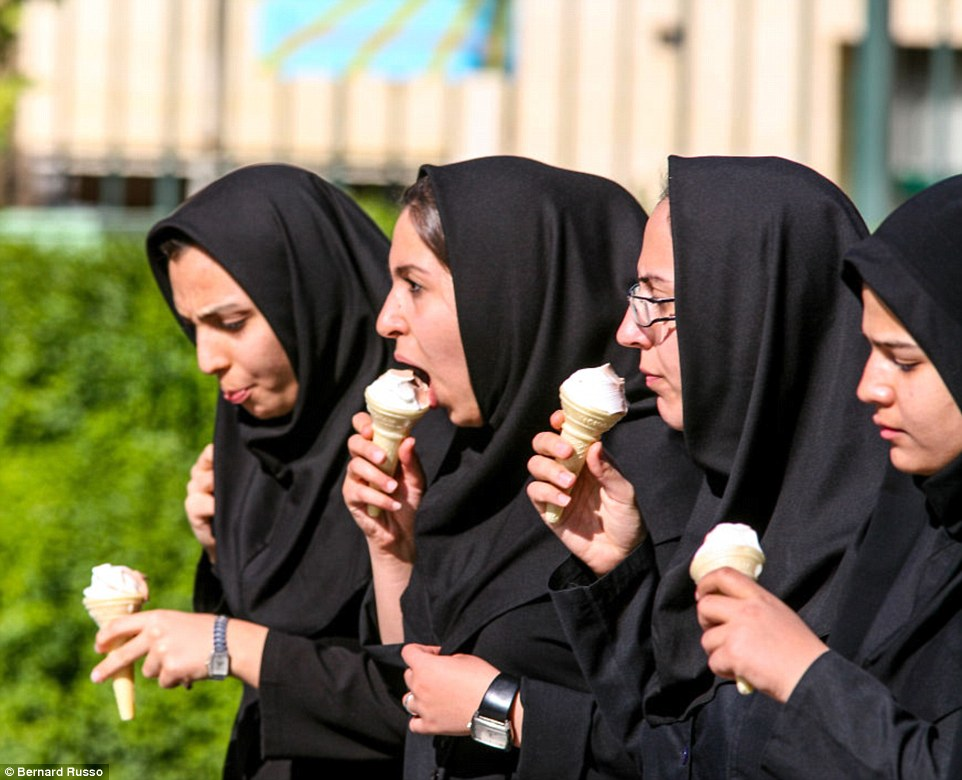 Young women relax with ice creams in the sunshine after school closes in Esfahan