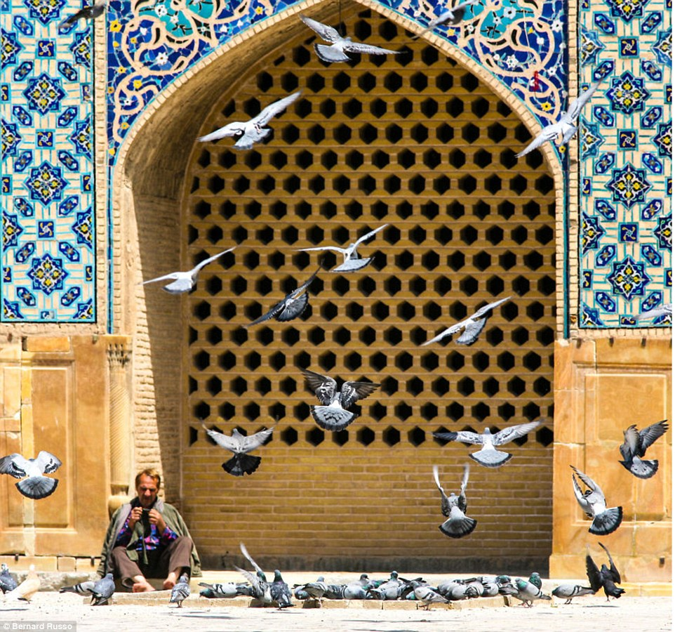 A young man sits among the pigeons on the pavement in Kashan framed by beautiful colourful architecture