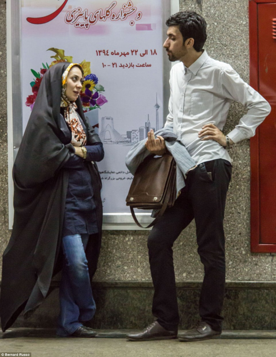 A young woman and man seem to flirt while waiting for a train on the Metro