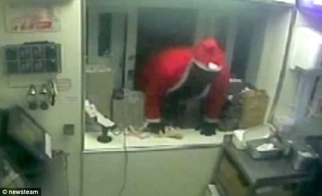 This is the moment a knife-wielding robber dressed as Father Christmas climbed through a KFC window before threatening staff and stealing cash
