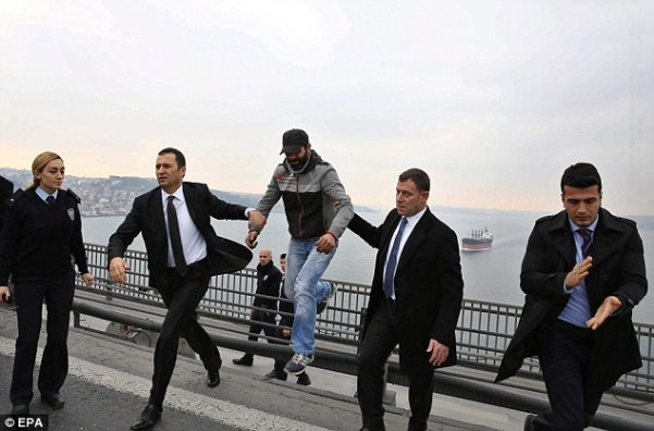 Two bodyguards escort the man, who was dressed in jeans and a simple hoody, to an official vehicle