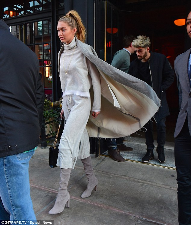 Caped crusader: While Gigi went for a light-coloured look in a pallet of almost entirely greys, Zayn rocked an entirely darker ensemble as he headed out of the building