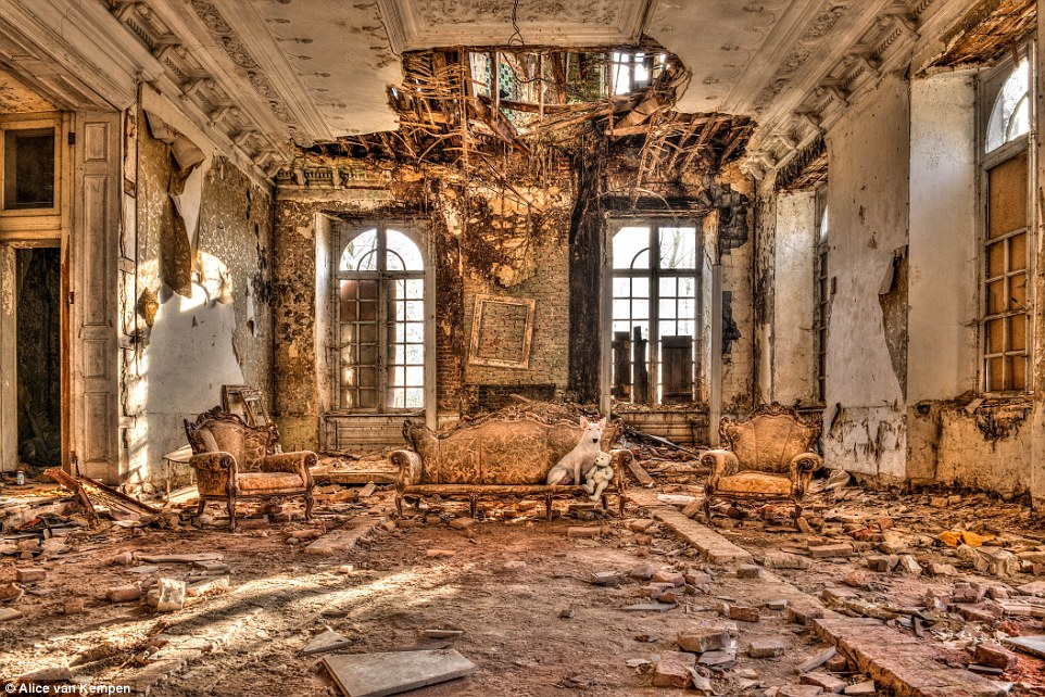 In the same castle, this room has seen better days. The ceiling droops down above Claire who sits beside a teddy bear on a luxury sofa