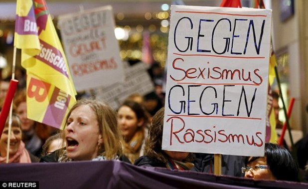 """Women shout slogans and hold up a placard that reads """"Against Sexism - Against Racism"""" as they march through the main railways station of Cologne"""