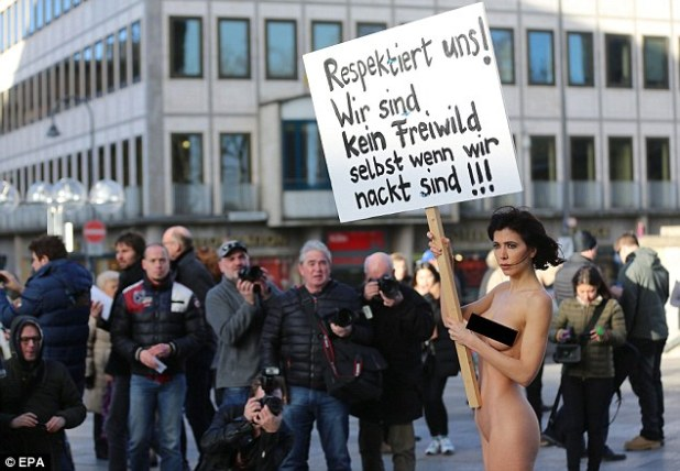Swiss artist Milo Moire holds a sign 'Respect us! We are no fair game even when we are naked!!!' as she protests naked in front of the Cologne today