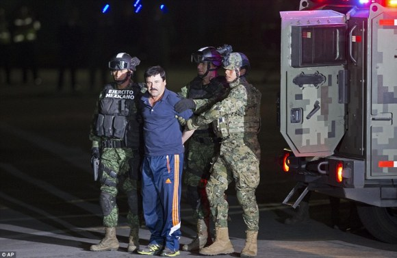 Notorious drug lord Joaquin 'El Chapo' Guzman has been sent back to the same prison he escaped from six months ago. Pictured, soldiers- showing their faces in full sight - march the drug lord to the Mexican attorney general's hangar at an air base in New Mexico