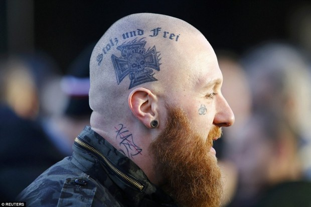 A supporter of anti-immigration right-wing movement Pegida sporting a tattoo reading 'Proud and Free' and the crossed out word Nazi