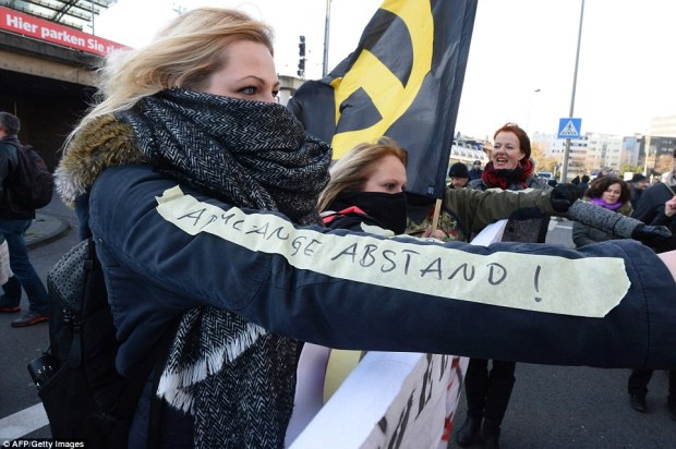 """A German far-right supporter demonstrates with a sticker reading """"an arm-length distance"""" referring to the suggestion of Cologne's mayor for women of how to behave to prevent being assaulted by men at Cologne's railway station"""