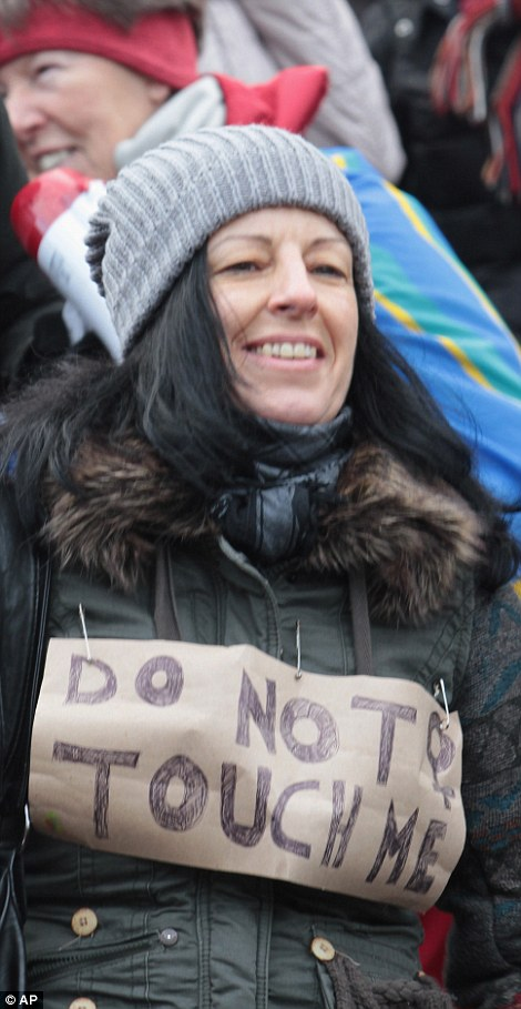 One female protester (left) holds up a sign saying, 'Hey racists! You are so disgusting! The world could live without you' while another (right) wears one saying 'do not touch'