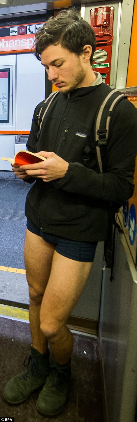 A man wearing no pants reads a book as he participates in the 'No Pants Subway Ride' in in Vienna, AUstria