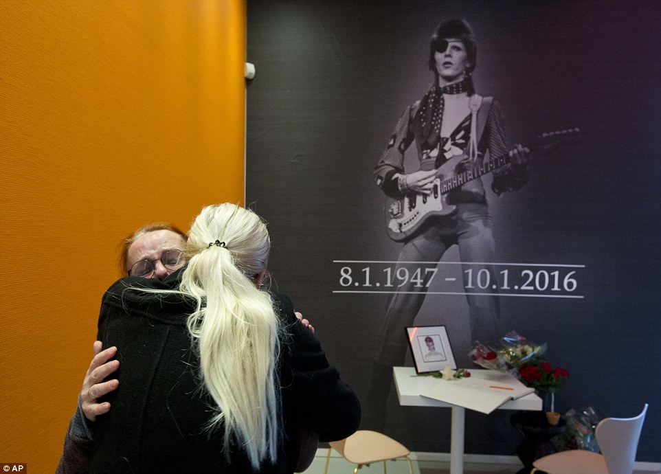 Embrace: Mourners at the Groninger Museum in the Netherlands, where an exhibition on Bowie's life and work is currently on display
