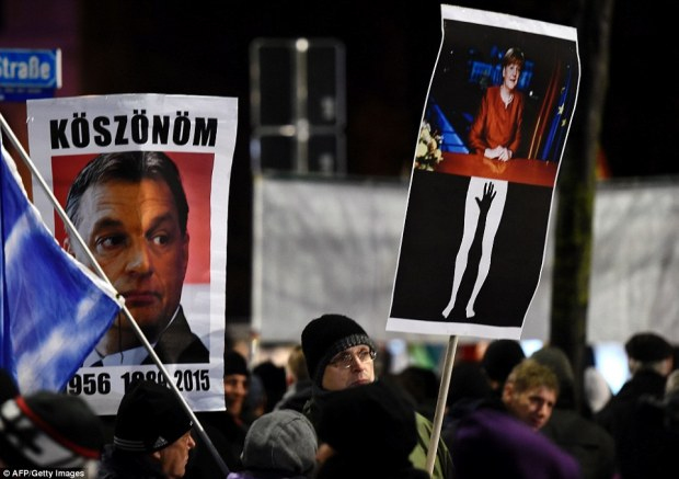 A poster of Chancellor Merkel and one of Hungarian prime minister Viktor Orban reading 'Thank you' is held aloft by a PEGIDA protester
