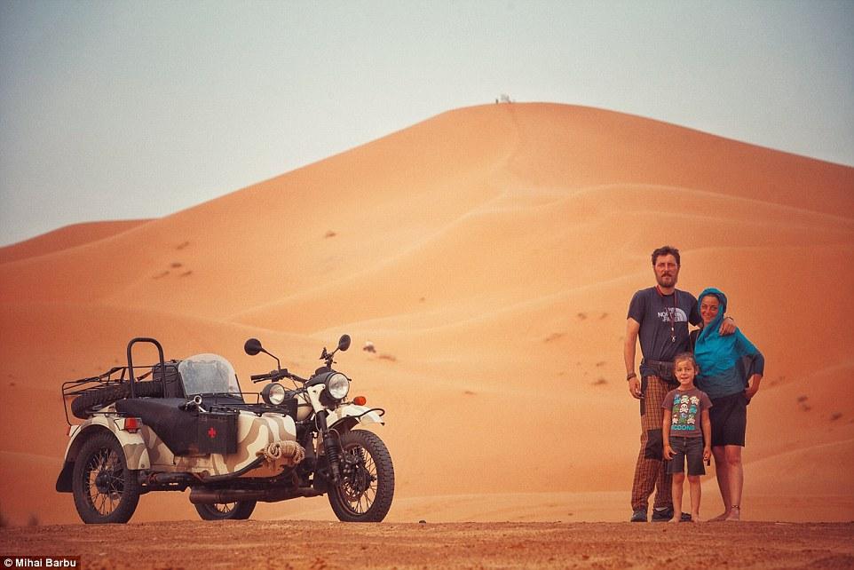 Fun in the sun: Photographer Mihai Barbu pictured with his girlfriend Oana and son Vladimir in the Sahara desert in Merzouga, Morocco