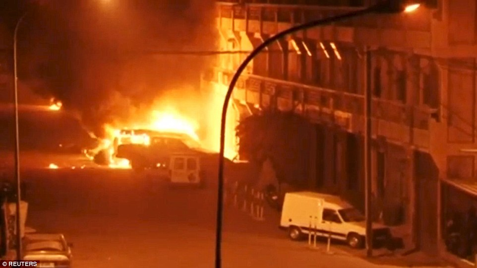 A view shows vehicles on fire outside Splendid Hotel in Ouagadougou, Burkina Faso during a siege by Islamist gunmen on Saturday