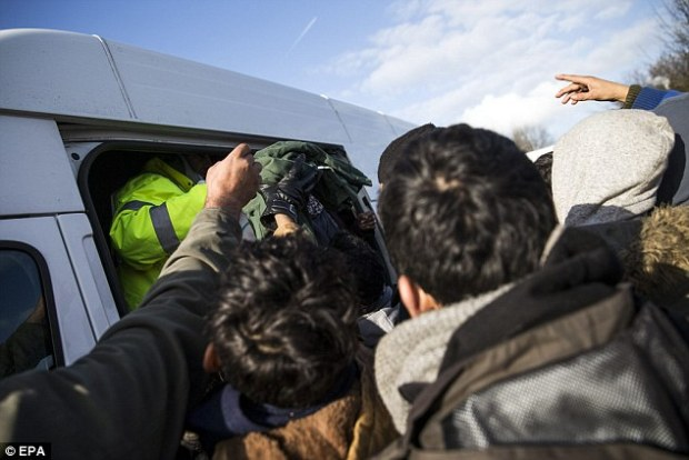 Volunteers distribute clothes to migrants in Grande-Synthe.Schaeuble warned that unless the migrant problem is dealt with, the crisis will balloon
