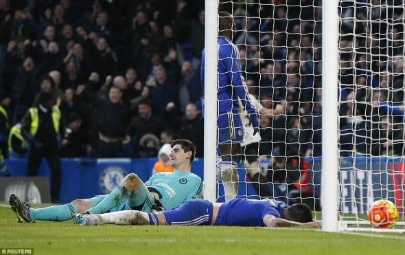 Chelsea captainJohn Terry lays face down on the turf after turning the ball past Thibaut Courtois who looks on with dejection