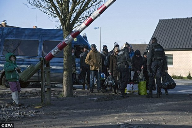 French police control volunteers and migrants as they enter the makeshift migrant camp in Grande-Synthe