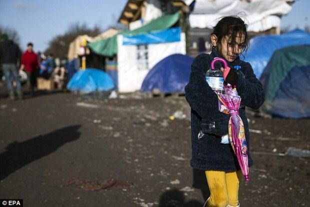 A young Kurdish girl walks along a muddy road clutching a pink umbrella, against a backdrop of tents