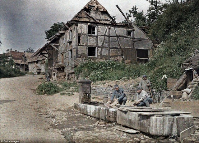 Two French soldiers assigned to a telephone station wash their laundry in a trough of a fountain, in Largitzen, France on 18 June 1917