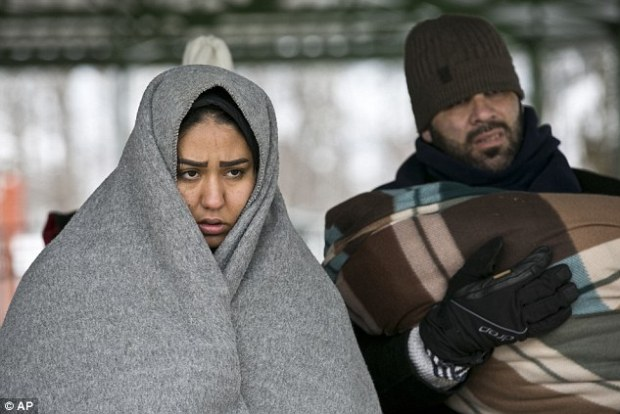 A migrant couple wait to be registered at the registration camp after crossing from the Macedonian border into Serbia, in Presevo