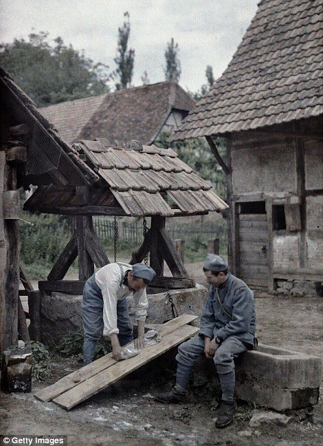 Two French soldiers are taking care of their laundry using boards set up on the trough of a fountain near a farm house in the town of Gildwiller, Department Haut-Rhin, Region Alsace on 21 June 1917