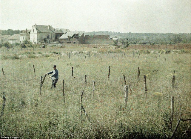 A French officer inspects the barbed wire around French positions in Soissons, which was heavily damaged by artillery fire during the war