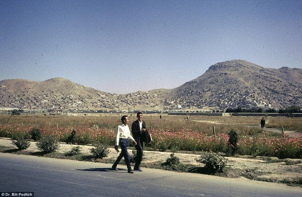 Not a bad commute: Young Afghans walking home with spectacular scenery visible in the distance