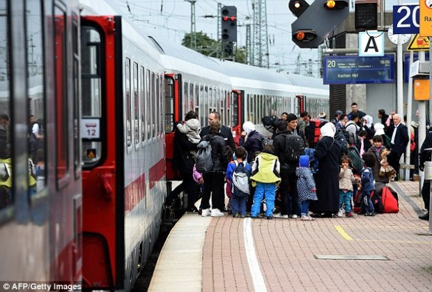 Spread around the country: Migrants are pictured arriving at the train station in Dortmund, western Germany
