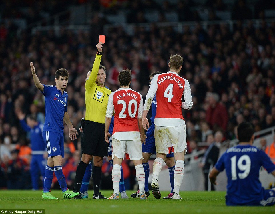 Mark Clattenburg shows Per Mertesacker the red card after the Germany international hauled down Costa as he ran through on goal
