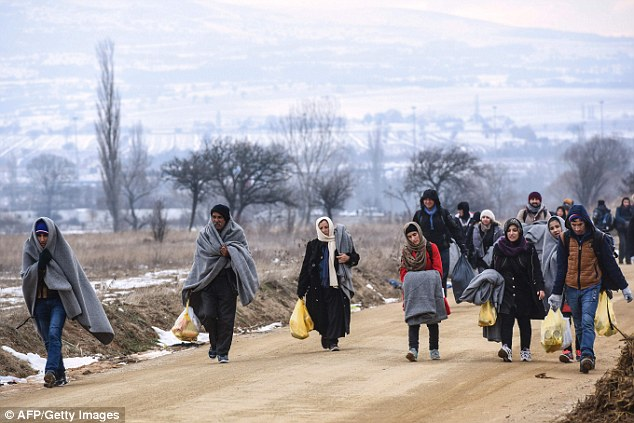 Slovakia, a eurozone member of 5.4 million people, has filed a lawsuit against the EU-proposed quota system for distributing migrants across the continent, just like neighbouring Hungary. Migrants are pictured walking across the Macedonian border into Serbia