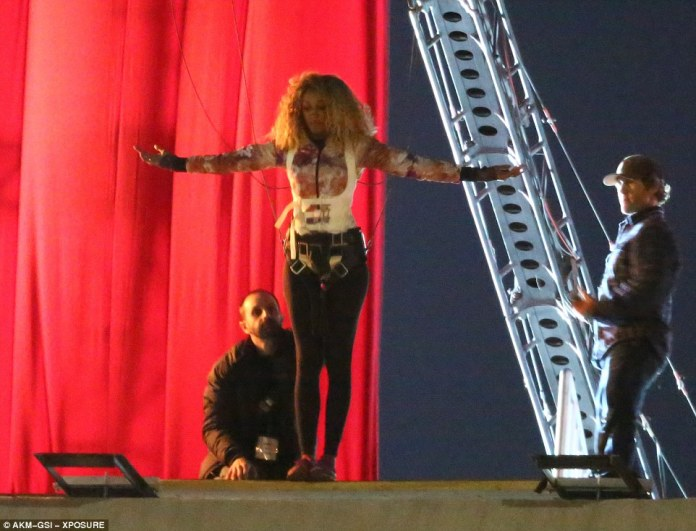 Looking bright: The caramel-haired body double, with similar curly tresses to Beyonce, sported a colorful, patterned zip-up jacket and black skintight trousers
