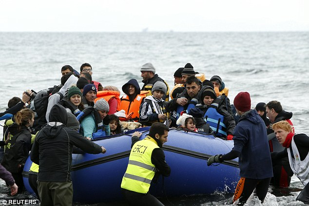 Volunteers pull a raft packed with refugees and migrants as they arrive on a beach on the Greek island of Lesbos on Friday. The Swedish police commissioner said an increasing number of officers were needed to deal with crime problems linked to migrants