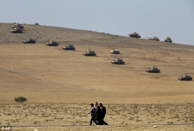 Turkish Kurds walk as tanks in the background hold their positions on a hilltop in the outskirts of Suruc, at the Turkey-Syria border, in 2014