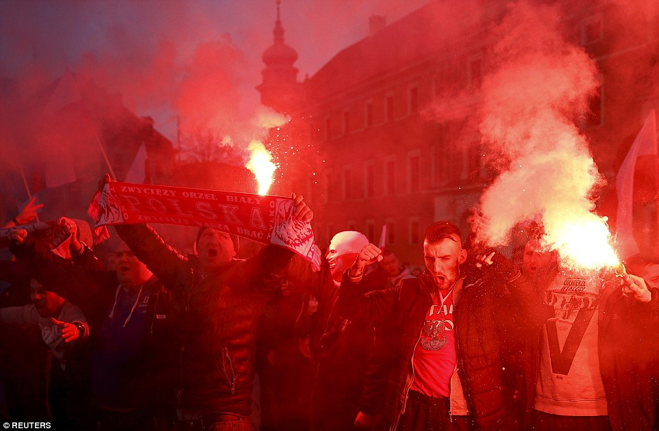 Protesters light flares, hold up Poland scarves and banners and shout slogans during an anti-immigrant rally in front of the Royal Castle