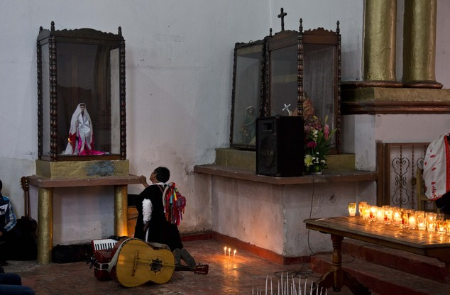 In this Jan. 17, 2016 photo, a Tzotzil Indian man prays in front of a religious image at the Church of San Pedro in Chenalho, Chiapas state, Mexico. The Vati...
