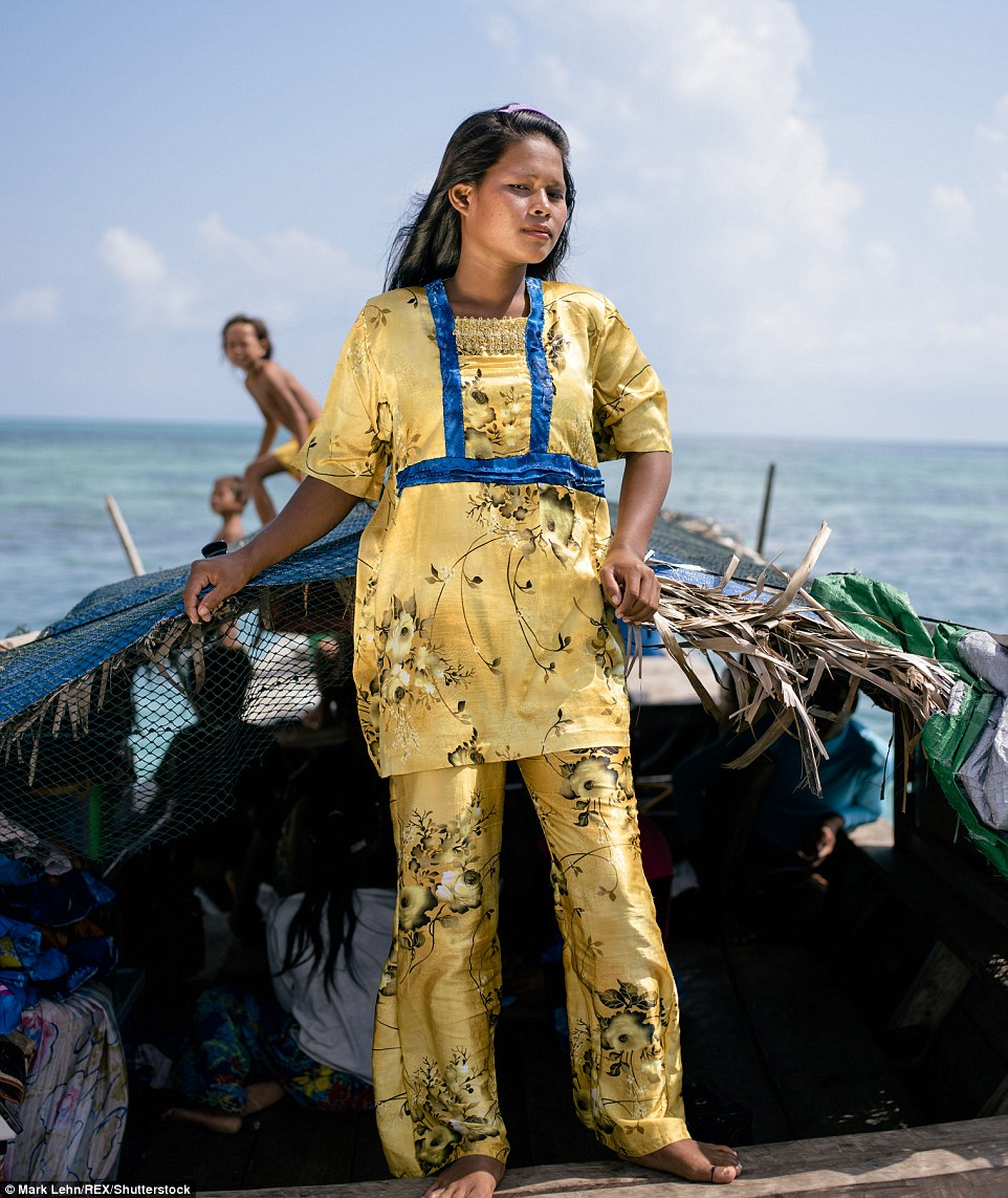 A Bajau Laut woman stands on her Lepa Lepa, or boat, near Bodgaya Island. They rely on the sea for trade and for food sources