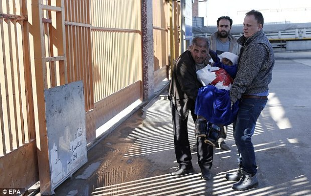 Three men assist an injured woman at the border crossing, which so far Turkey has refused to open