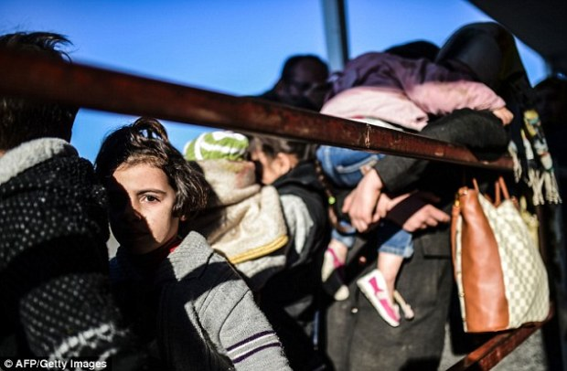 Syrian families wait at the border crossing after being unsuccessful in their attempts to enter Turkey