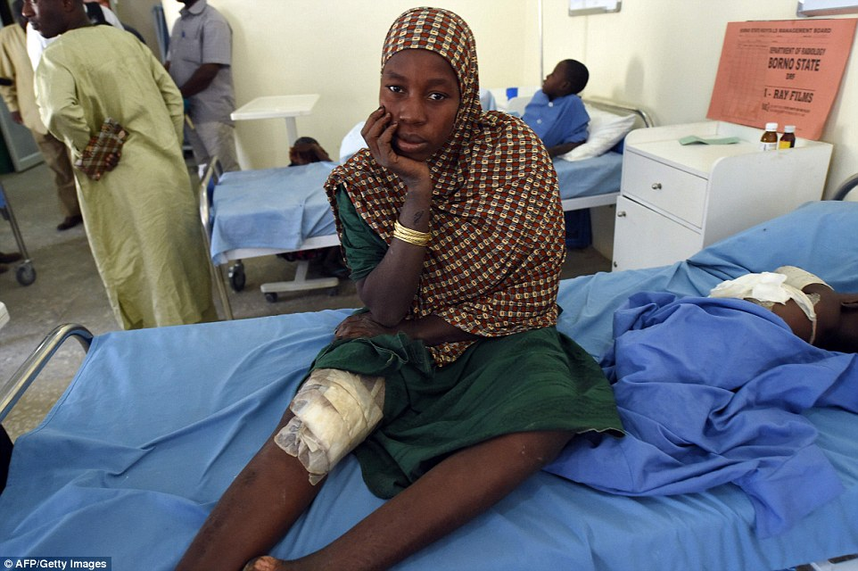 A mulher senta-se em uma cama enquanto espera para tratamento médico após um ataque Boko Haram em uma enfermaria de hospital em Maiduguri, Nigéria